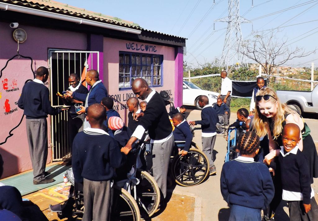 The Learners at Mason Lincoln gather round to make their own hand prints on the mural