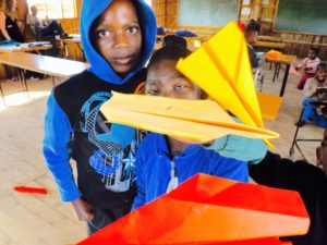 Three of the learners at Mason Lincoln with their paper airplanes.