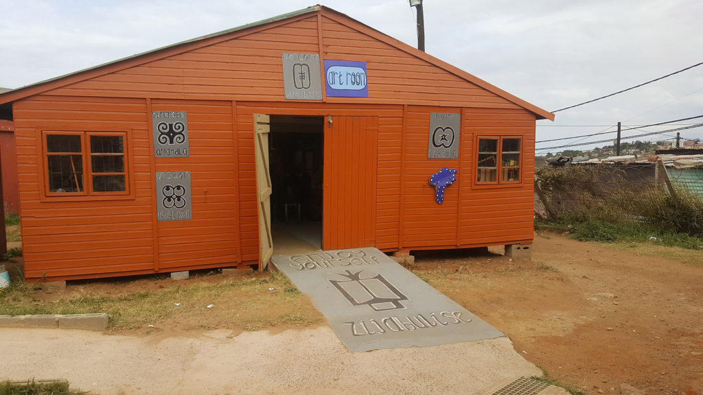 10. Mason Lincoln School Art Room Outside: A single storey wooden hut with a ramp two small windows and a single door.