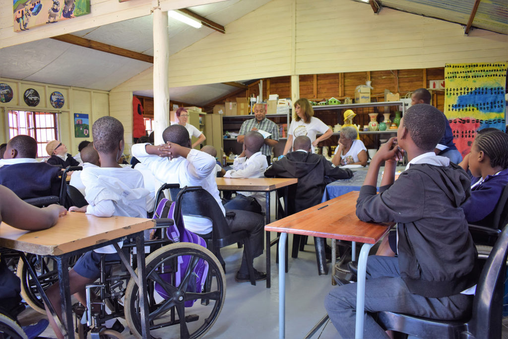11. Mason Lincoln School Art Room Inside (a): Learners sit at desks and look towards Njabulo and Jean as they explain what they will do today.