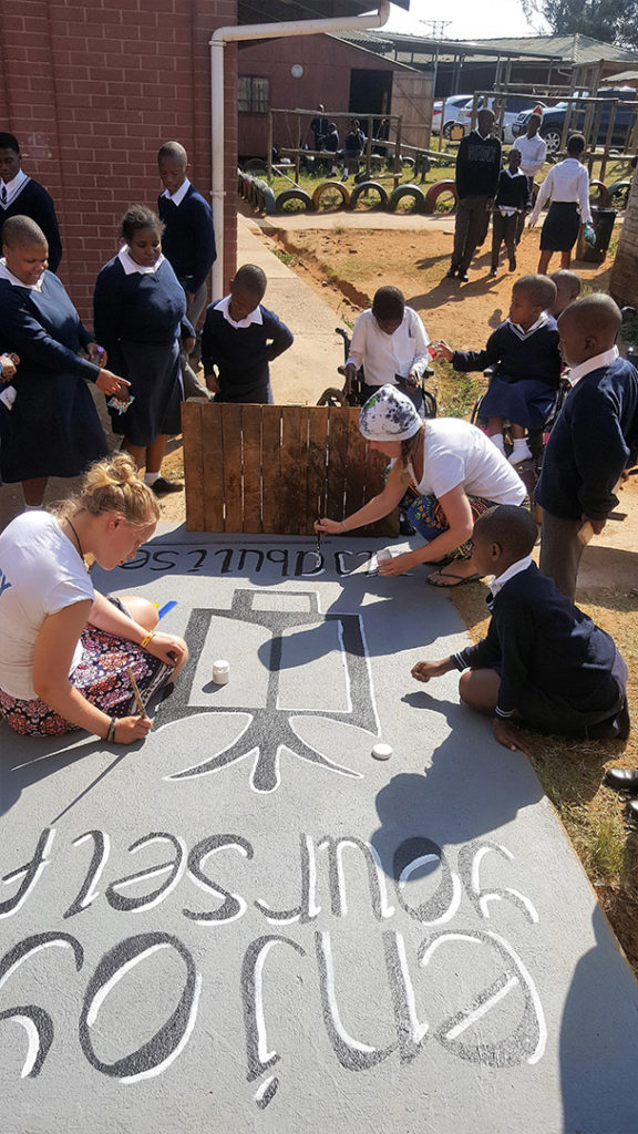 15. Mason Lincoln Art Room Entrance (b): Surrounded by learners, Lucy sits on the ramp while Suzi kneels to paint an African symbol – enjoy yourself - on the ramp.