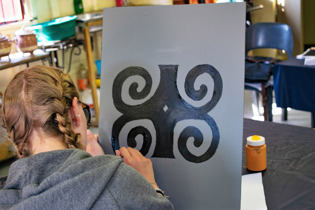 17. Mason Lincoln Art Room inside African Symbols: Lucy painting African symbol in black on grey wooden board.