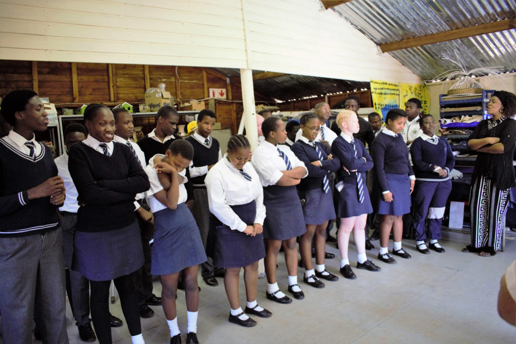 22. Mason Lincoln Art Room inside singing: The school choir of twenty learners in their uniforms form a semi-circle and sign at the back of the art classroom.
