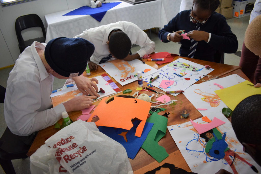 23. Mason Lincoln Braille Unit Art Class (a): Four visually impaired learners lean over a table covered in foam, paper, string, leaves and other objects making tactile art.