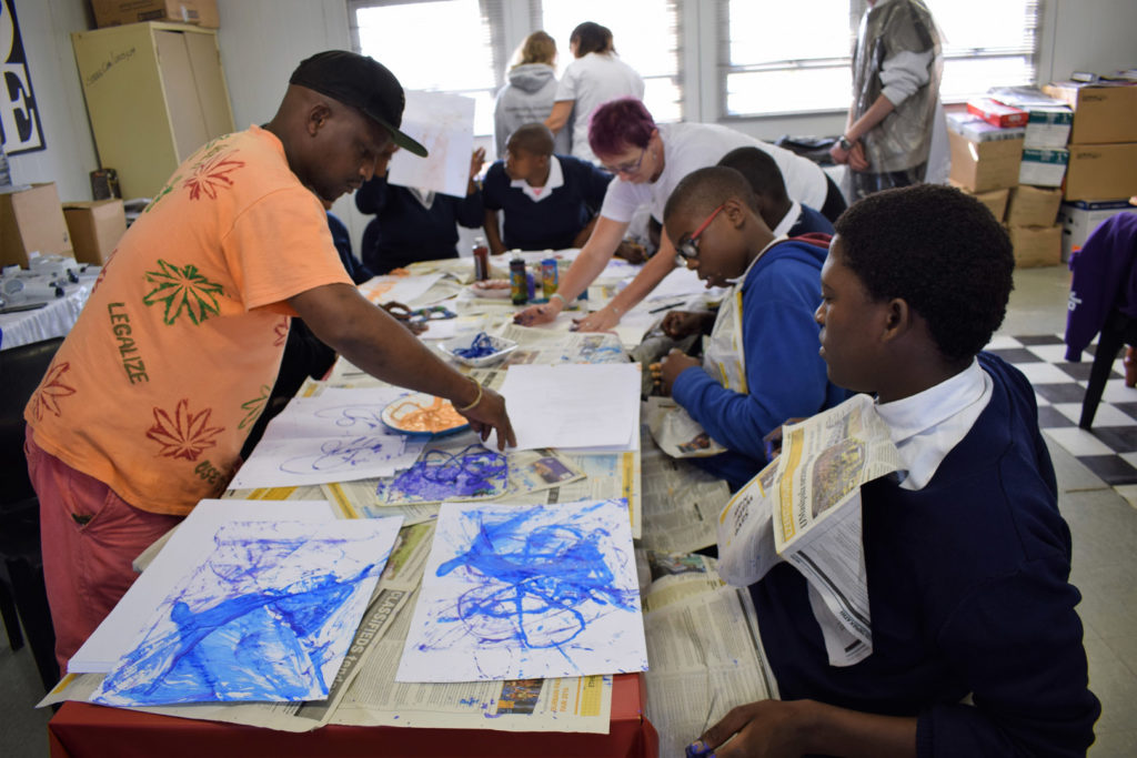 26. Mason Lincoln Braille Unit Art Class (d): Mxolisi and Jo and five visually impaired learners bend over a table covered with sheets of paper with blue string designs.