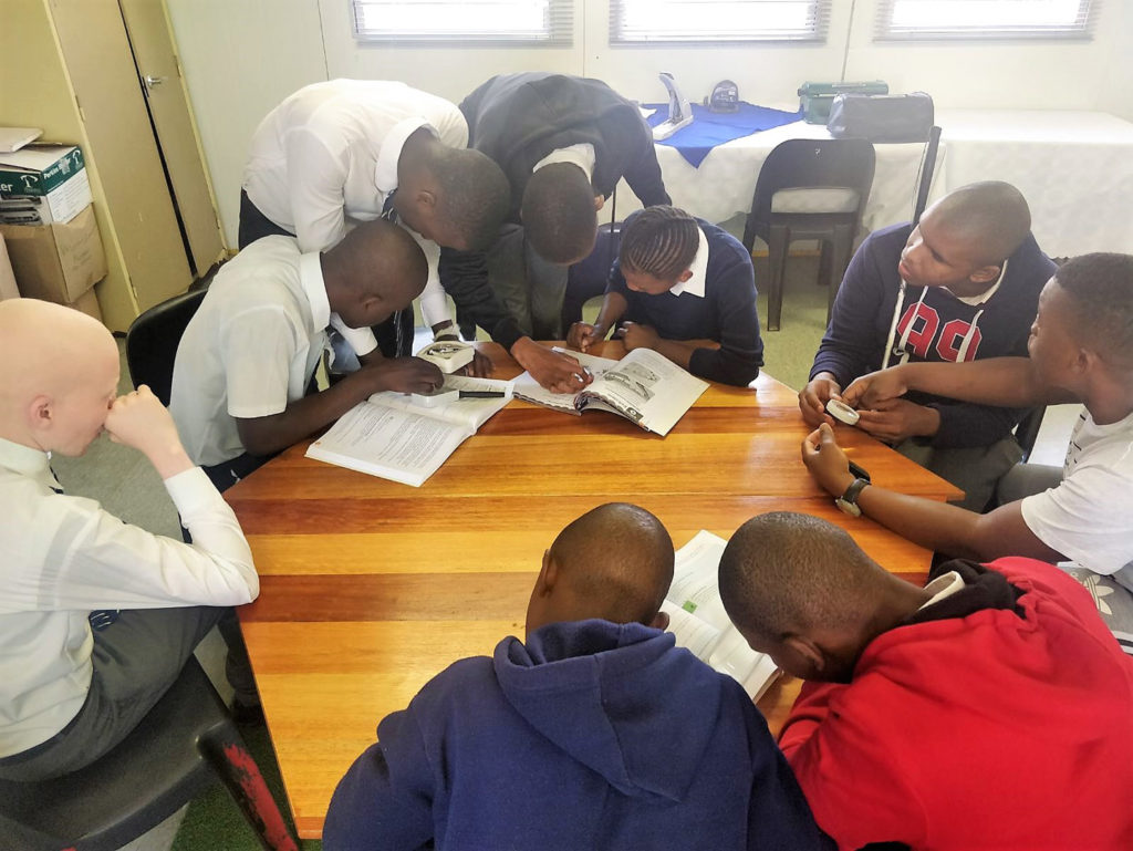 29. Mason Lincoln Braille Unit Trying magnifiers from RNIB (b): Eight learners crouch closely together looking at books through the magnifiers.