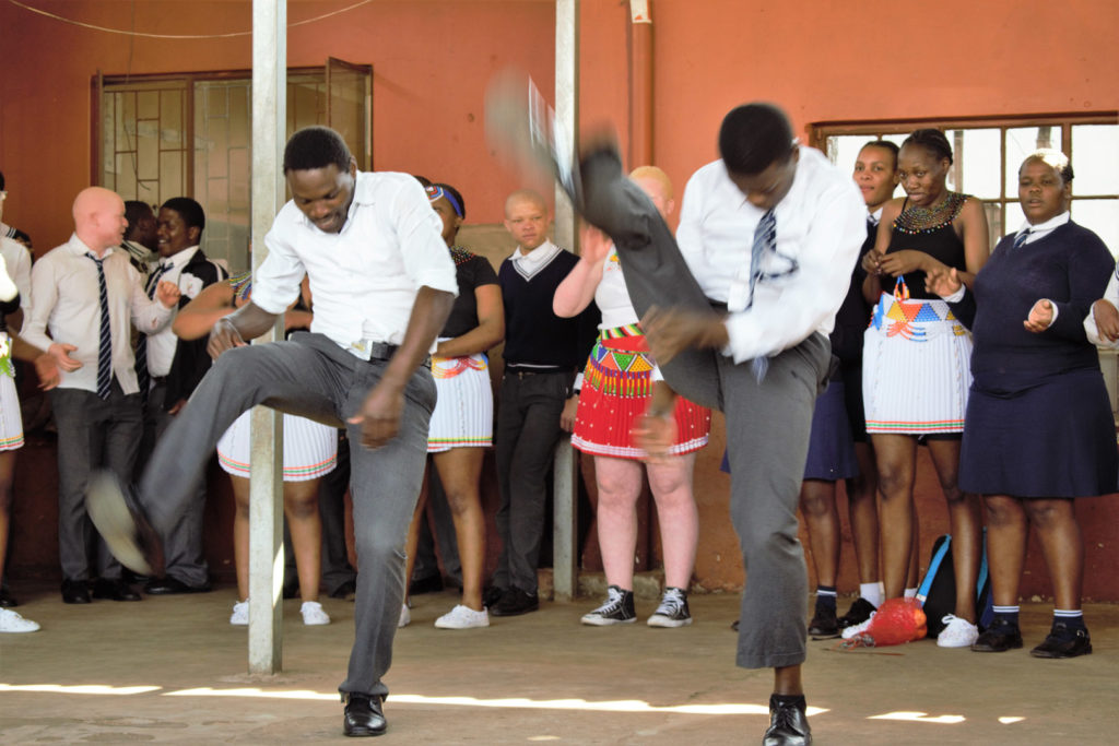 30. Mason Lincoln outside celebrating choir award (a): Two Young men in school uniform kick one leg above their heads in typical Zulu dance step to celebrate the choir's competition as the rest of the choir look on from behind them.