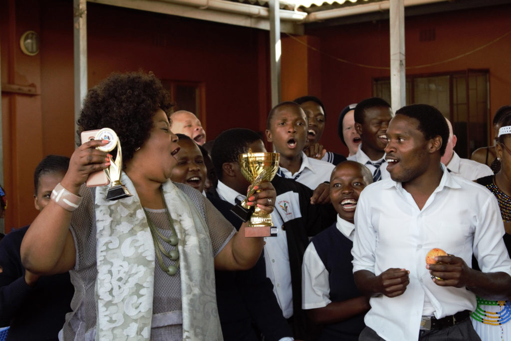 32. Mason Lincoln outside celebrating choir award (c) The Principal turns to the members of the choir and signs with them in celebration