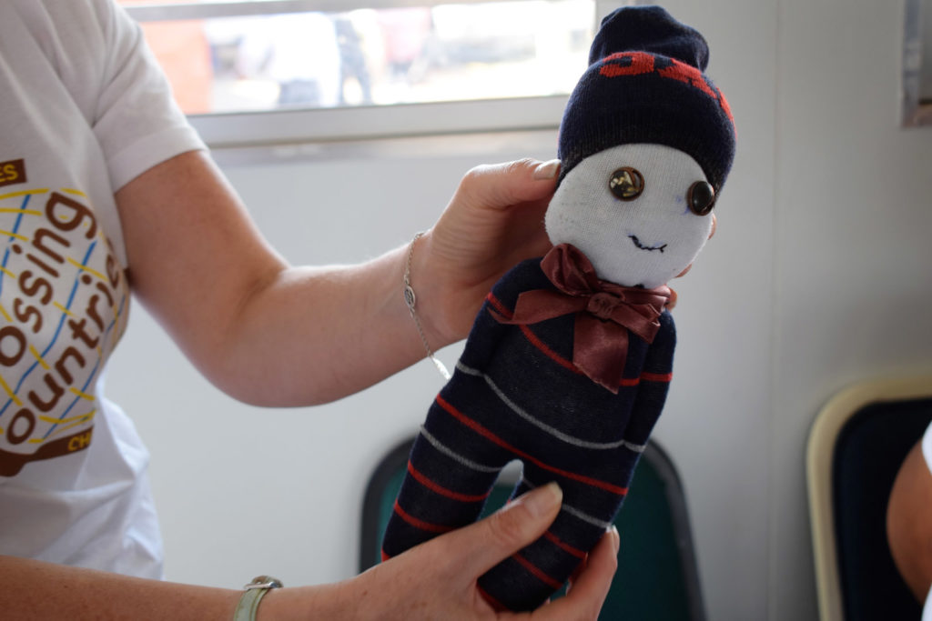 34. Mason Lincoln Skills class Sock Doll (a): Close up of doll with smiling face made from one white sock (face) and stripped sock (body and hat).