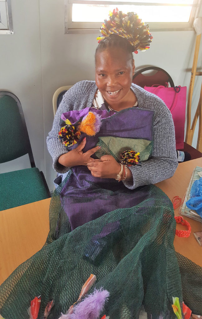 36. Mason Lincoln Skills class Thandjwe modelling her recycled fashion. Thandjwe sits on a chair with a pom-pom hat made from strips of colourful plastic and a dress made from green garden net decorated with colourful plastic pom-pom flowers.