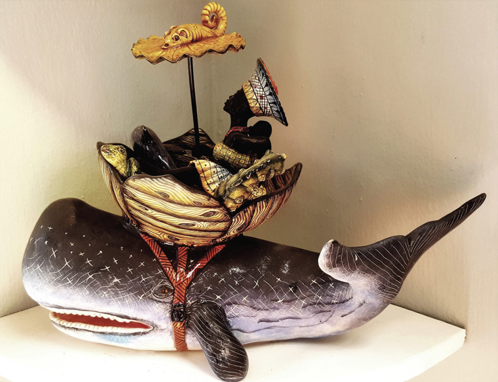 50. Ardmore Ceramics Whale: A black woman with her traditional head dress, holding her baby and an umbrella sits in round boat strapped to the back of a whale.