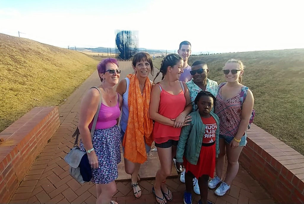 52. Howick Nelson Mandela Capture Site the team: The team with Mzukulu's daughter, Thando, pose in front of the Nelson Mandela sculpture, its vertical black strips rise to reveal the face of Madiba.