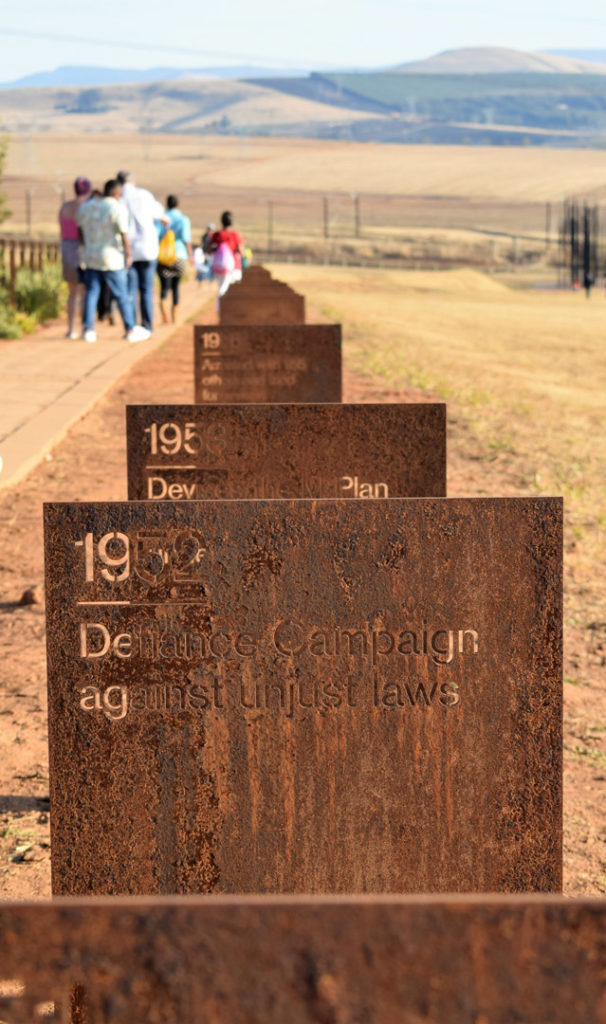 53. Howick Nelson Mandela Capture site time line: Rusting metal rectangles etched with events from Mandela's life follow the path tourists walk towards the sculpture with the hills in the background.