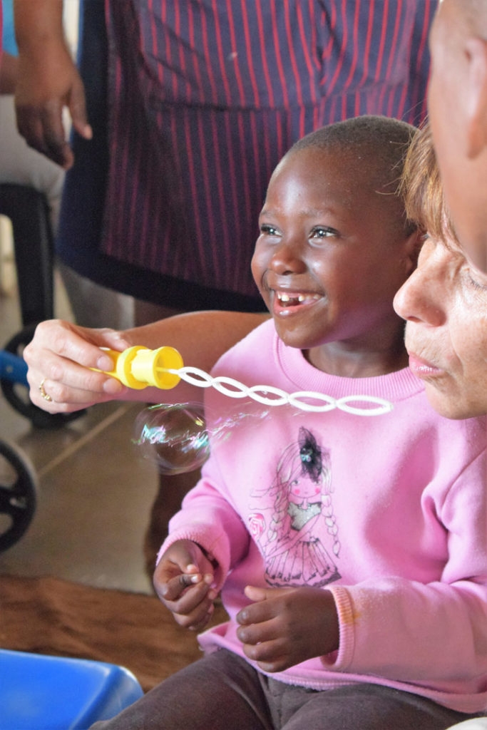 55. Ikwhezi Bubbles (a): Close up of Jean blowing bubbles with smiling child sitting next to her.
