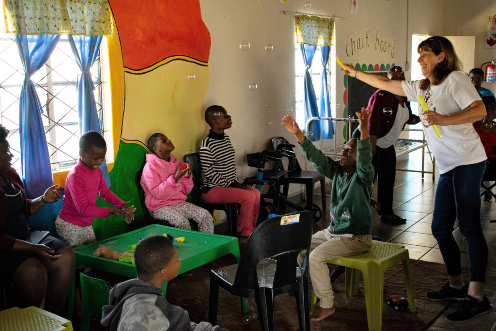 57. Ikwhezi Bubbles (c): Children sit waving their arms and looking up on stools and chairs, Jean reaches forward to waft bubbles to them.