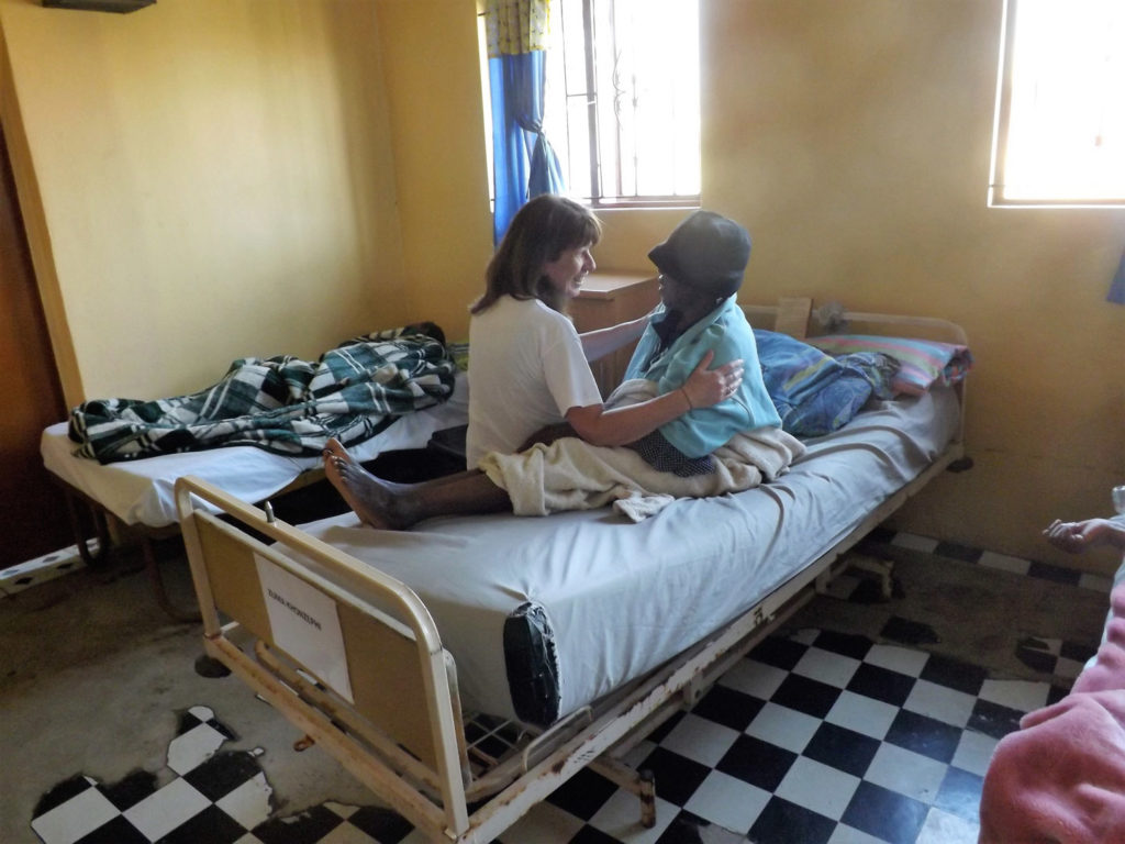 58. Ikwhezi Elderly people unit: Jean sits on hospital bed facing elderly lady with hat, they are talking and holding each other.