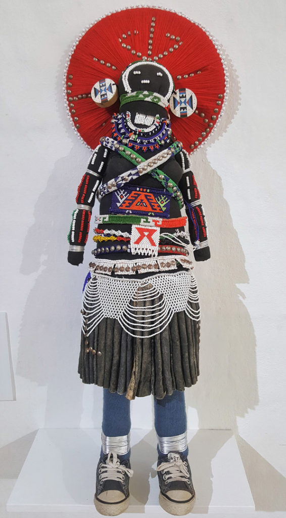 60. Art Large Makoti Doll by Lobolile Ximba self portrait of married woman passing on her wisdom about AIDS: A doll dressed in a traditional black and white costume with the addition of jeans and sneakers. She also wears a large red circular head dress.