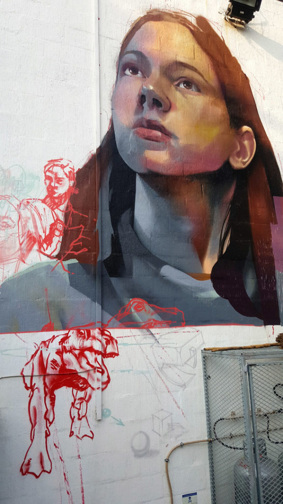 62. Art Graffiti KZN Art Gallery: Realistic painting of young woman with red hair stares from the white wall into the sky.