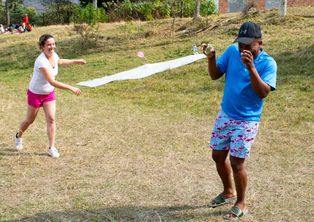 64. Bobbi Bear water fight Demonstration Suzi and Mzukulu: Suzi throws a water balloon at Mzukulu who turns away raising his hands to hide his face.