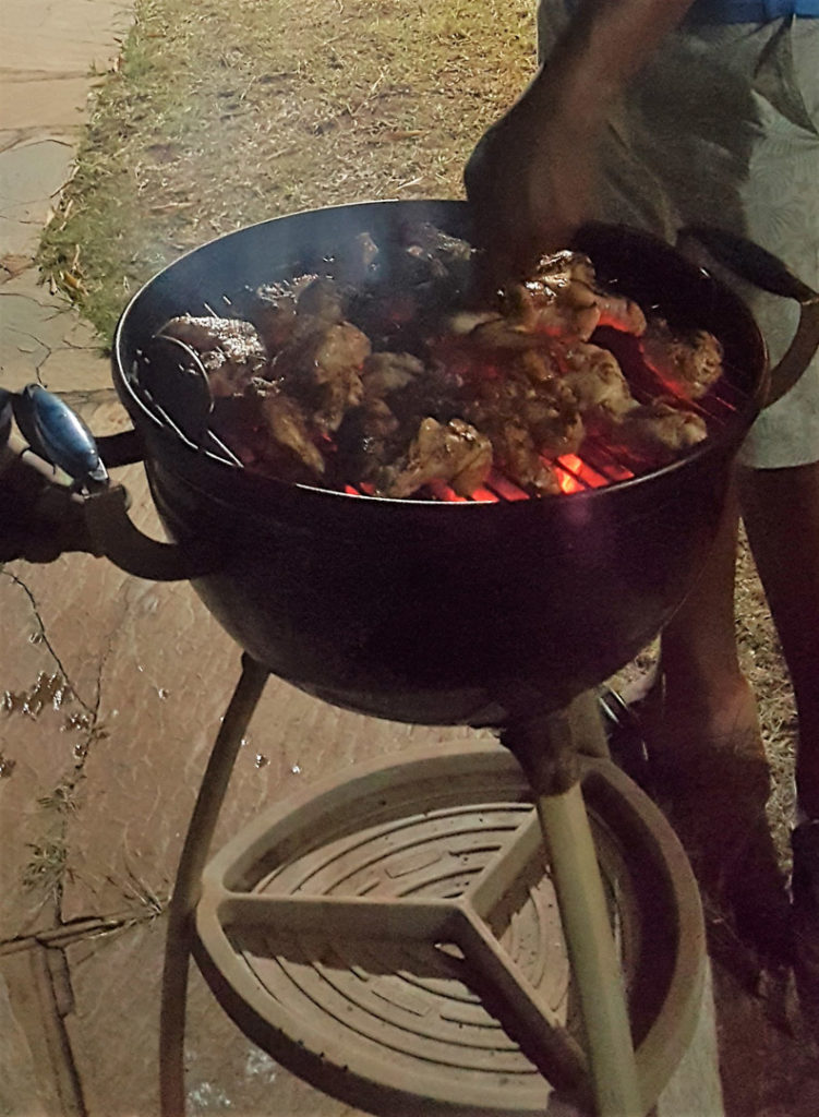 78. Food Braii Mzukulu cooking: Close up of kettle barbeque and Mzukulu's hand as he turns the meat.
