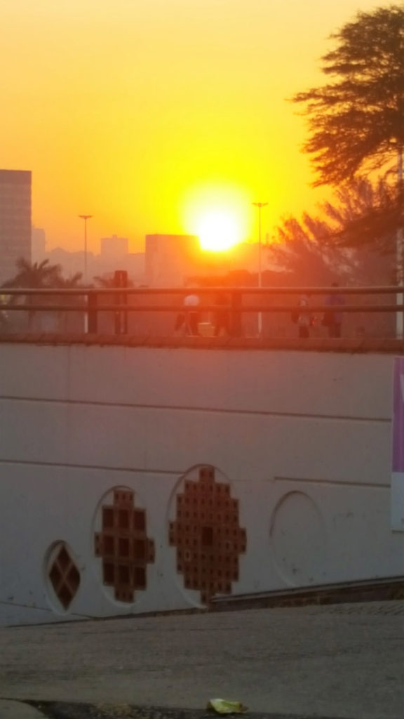 83. Sunset Durban: The bright sun sets behind the modern towers above a walk way in Durban