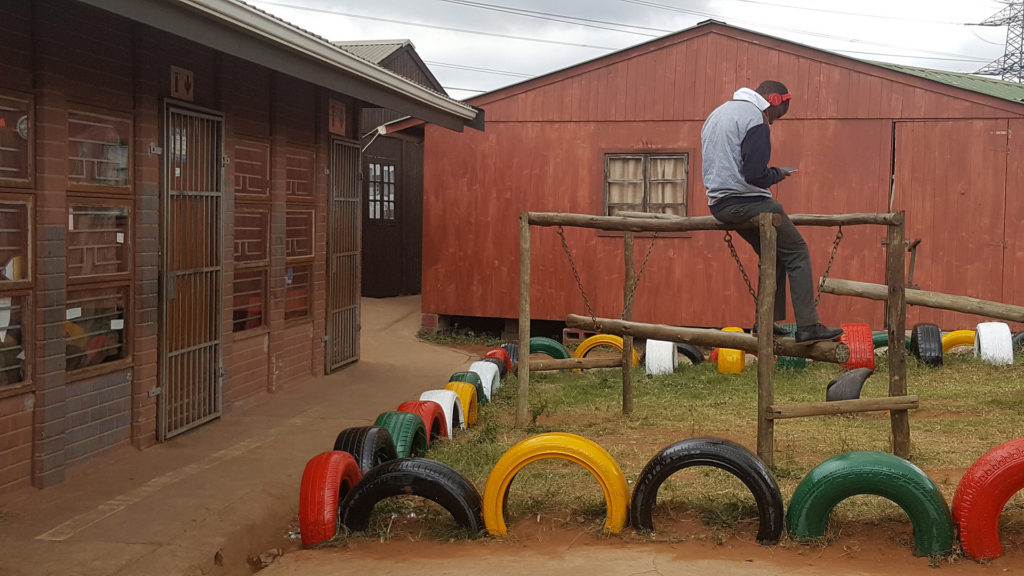 9. Mason Lincoln School: In the centre of two wooden huts a teenager sits on the wooden beam of a climbing frame. The area is surrounded by half buried coloured tyres.